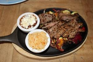 Fajitas con Steak Arrachera, mariniertes Entrecote vom Rind, serviert auf heißer Platte mit frischer Guacamole, Frijoles Borrachos (Bohnenmousse), Verduras Asadas (geröstetes Gemüse) und Weizentortillas