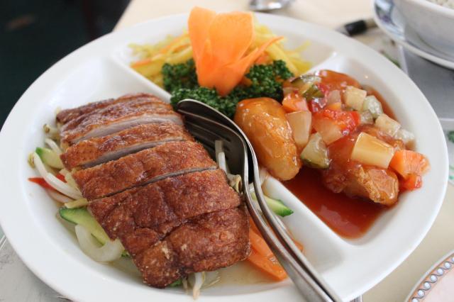 Abendmenü: Knusprig gebackene Ente mit Gemüse in pikanter Sauce und gebackenes Hühnerfleisch süß-sauer mit Salatgarnitur